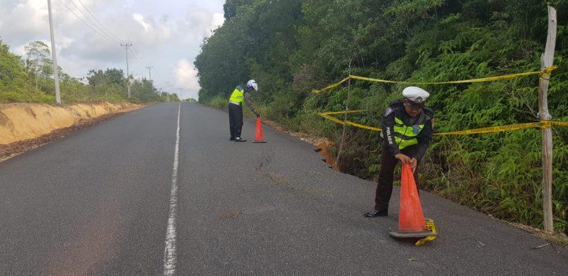 Tampak 2 anggota Satlantas Polres Bintan sedang memasang Trafikun dan Police line