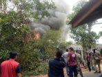 Tim Satpol PP dan Damkar saat berupaya memadamkan api yang melahap salah satu rumah di bawah pohon kayu Are