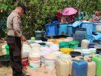 Bripka Yahabibi saat membantu penyaluran air bersih ke warga Kp Melayu Kelurahan Senggarang