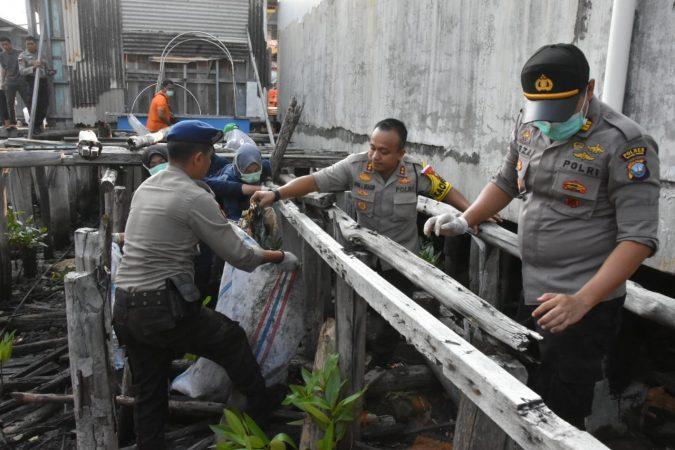Tampak Kapolres Tanjungpinang AKBP Ucok Lasdin Silalahi membersihkan sampah di bawah pelantar tanpa menggunakan sarung tangan