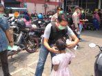 Kanit Reskrim Polsek Tanjungpinang, Iptu Adrian Saat Memasangkan Masker Kepada Salah Seoarang Anak di Depan Swalayan. Foto Istimewa