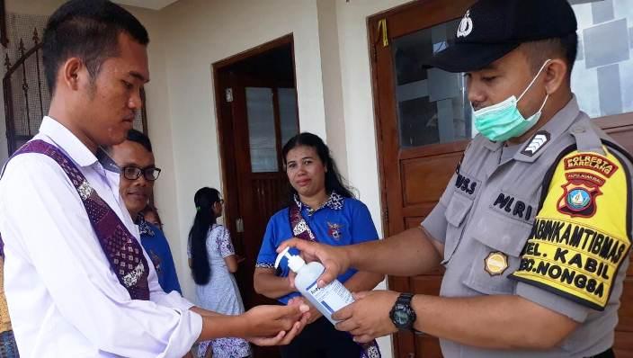Babinkamtibmas Kelurahan Kabil Saat Memberikan Cairan Pembersih Tangan Kepada Salah Satu Jemaat Gereja