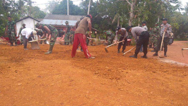 TNI-POLRI dan Warga Berjibaku meratakan tanah yang akan dibangun jalan sepanjang 1 Km melalui TMMD ke-107