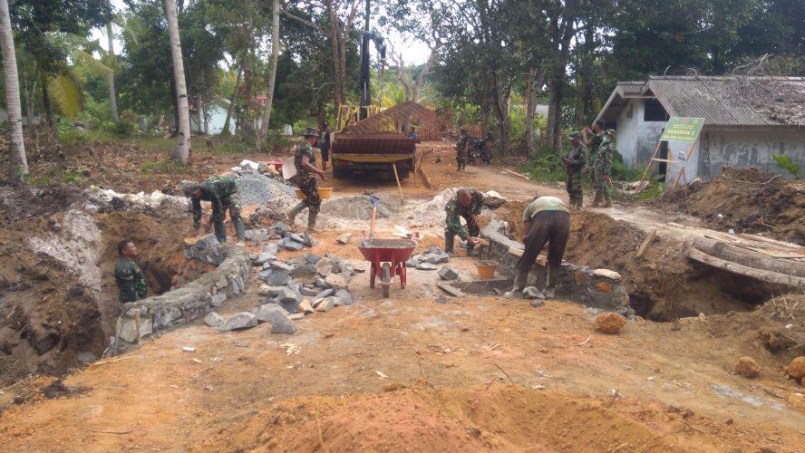 Prajurit TNI saat mengerjakan pekerjaan pembangunan jalan semenisasi sepanjang 1 Km lewat program TMMD ke-107 di Kampung Tanjung Siambang, Dompak