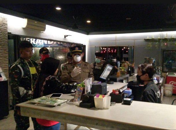 Anggota Satpol PP bersama tim gabungan TNI-POLRI saat memberikan pemahaman kepada salah satu cafe di Tanjungpinang