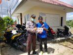 Babinkamtibmas Kelurahan Pinang Kencana Aipda Gafur memberikan selebaran Maklumat Kapolri ke warga