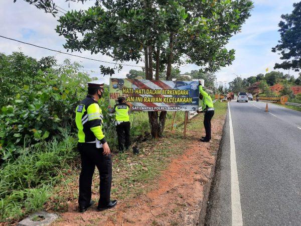 3 orang personil Satlantas Polres Bintan memasang spanduk hati hati di pinggir jalan Linbar Kabupaten Bintan