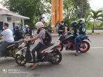 Pendiri Komunitas TTC Alpian Tanjung saat membagikan handsanitizer dan masker ke masyarakat pengguna jalan di Tanjungpinang