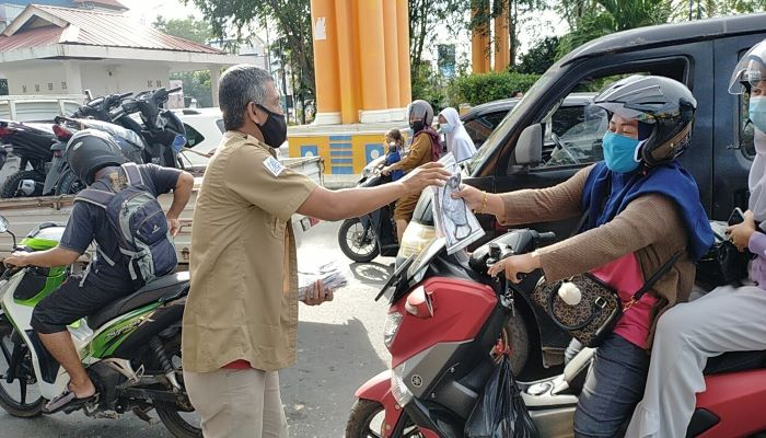 Ketua SMSI Kepri, Zakmi Saat Membagikan Masker ke Pengendara Sepeda Motor